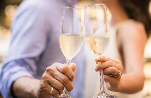 A couple facing each other, each holding out a flute of champagne
